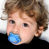 Toddler with a pacifier in his mouth.